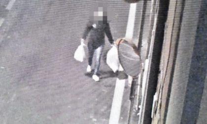 Butta i sacchi dei rifiuti per strada, ma le telecamere la beccano